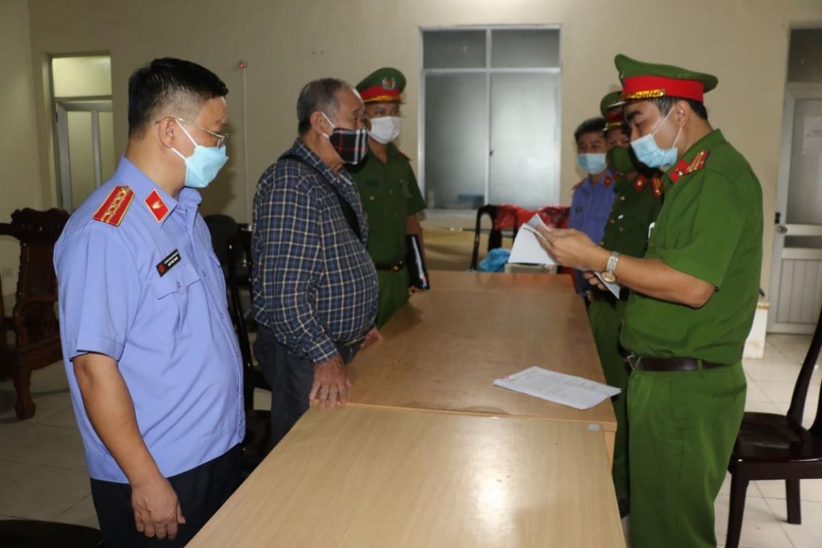 Cơ quan chức năng tống đạt quyết định khởi tố bị can và thi hành lệnh bắt tạm giam đối với ông Nguyễn Đình Khang. Ảnh CANA.